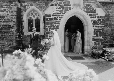 bride and groom exit a church holding hands after their wedding
