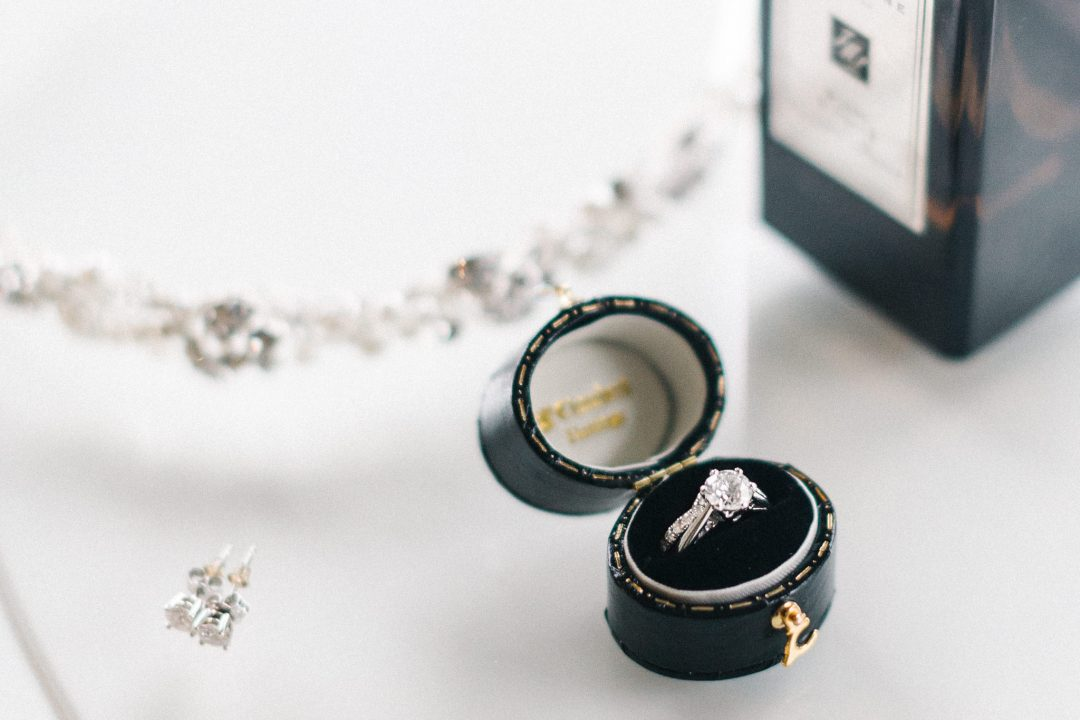bride's engagement ring in a velvet box on a white table next to diamond earrings and a bottle of perfume Somerley House