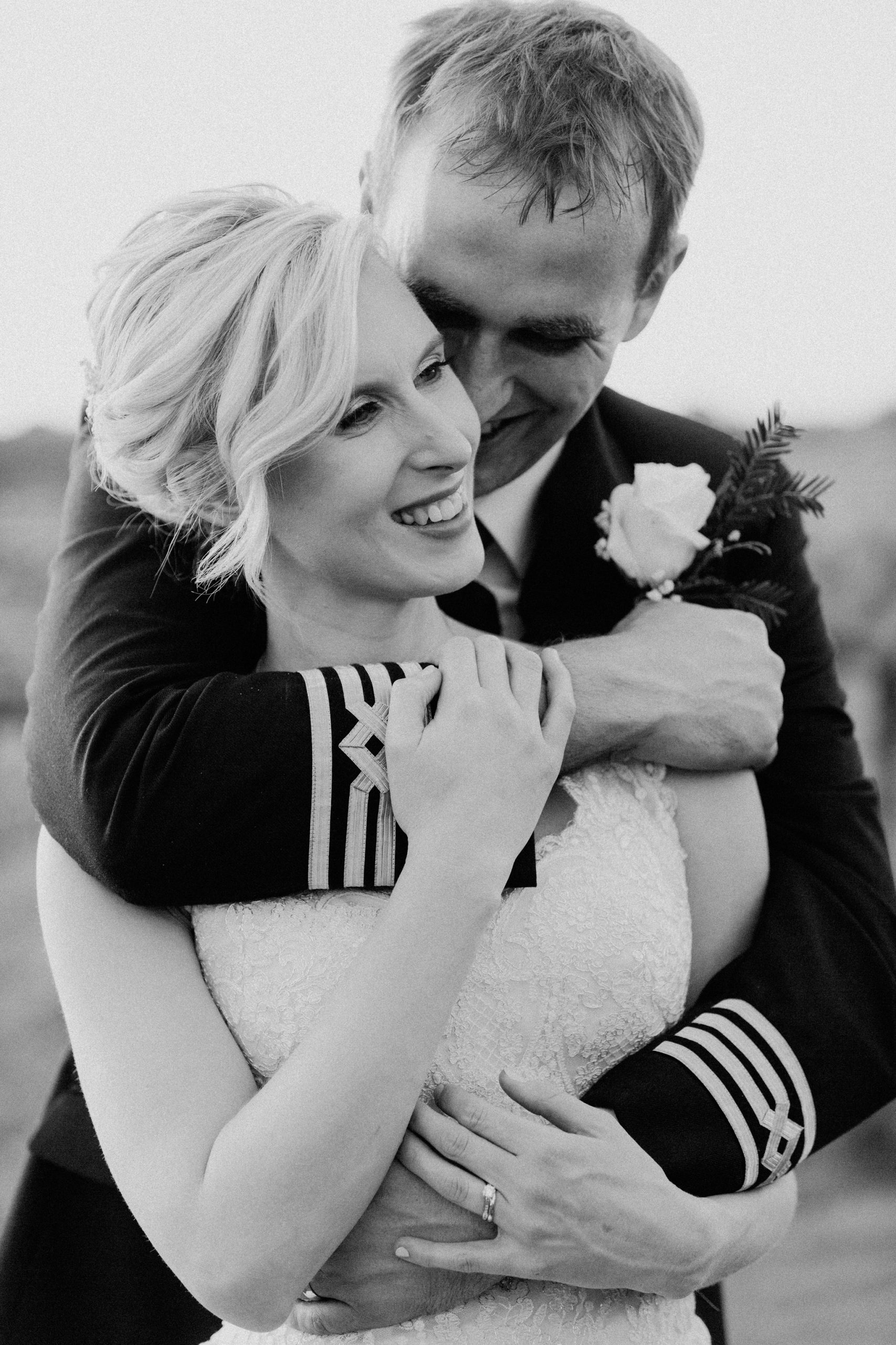 up close of bride and groom embracing and laughing at Three Choirs Vineyards